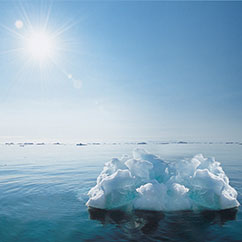 sun beating down on lone iceberg