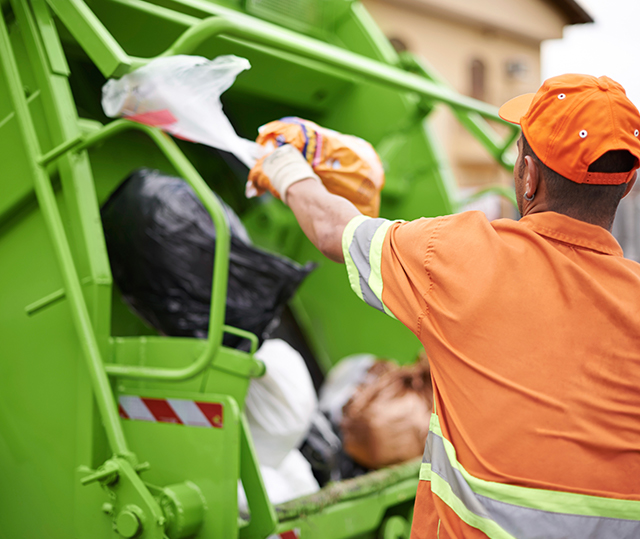 waste collector behind disposal truck